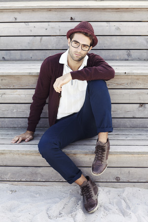Mid adult man in hat and cardigan on beach Standard-Bild