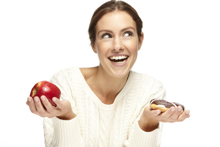 What to choose  Healthy or unhealthy  Portrait of a beautiful young woman choosing between an apple or a donut  On a white background photo