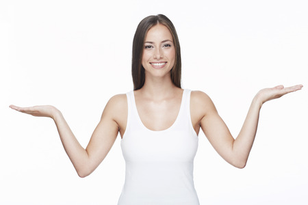 Portrait of young woman with arms out against white background photo