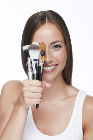 obscured face: Young woman holding make-up brushes against white background Stock Photo