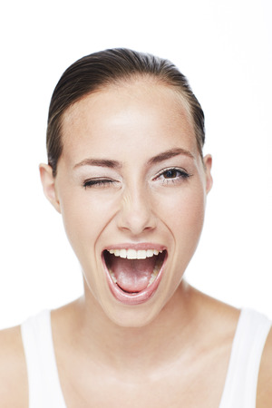 woman mouth open: Portrait of young woman winking against white background