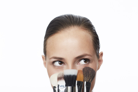 make up brushes: Young woman holding selection of make up brushes