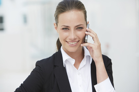 Young businesswoman using cellphone, smiling photo