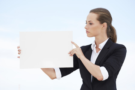 rolled up sleeves: Young businesswoman looking at blank sign Stock Photo