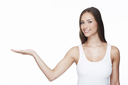 Portrait of young woman with arm out against white background photo