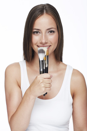 Young woman holding make-up brushes against white background photo