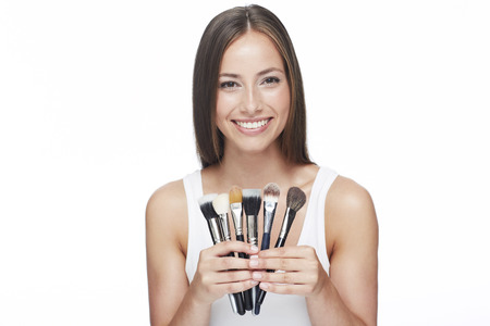 Young woman holding make-up brushes against white background Stock Photo