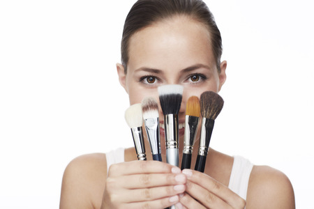obscured face: Young woman holding selection of make up brushes, portrait