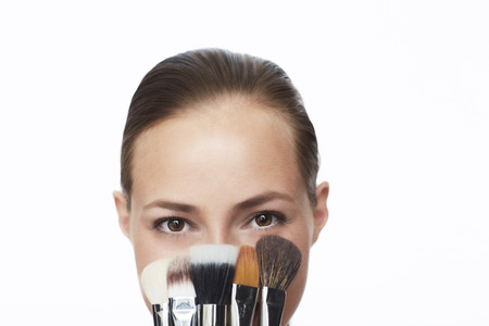 make up brushes: Young woman holding selection of make up brushes, portrait
