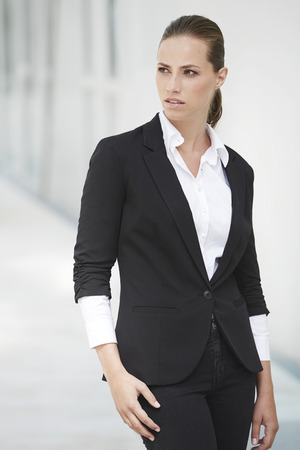 Young businesswoman in black looking away Stock Photo