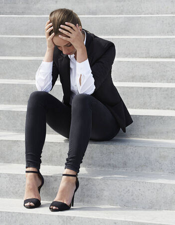 bad hair day: Young businesswoman sitting on steps with head in hands