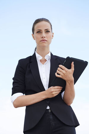 rolled up sleeves: Young businesswoman holding digital tablet against blue sky