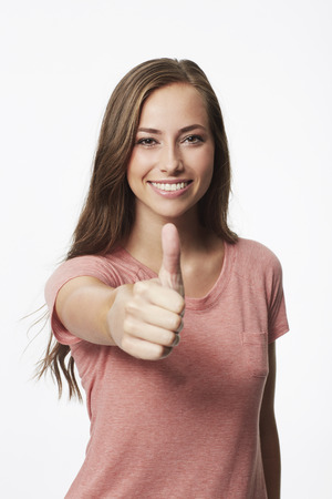 Portrait of young woman with thumbs up in studio
