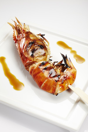 jumbo shrimp: Jumbo shrimp on stick lying on a plate.