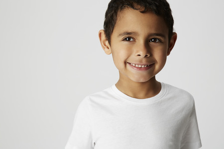 cheeky: Boy with cheeky grin in studio Stock Photo