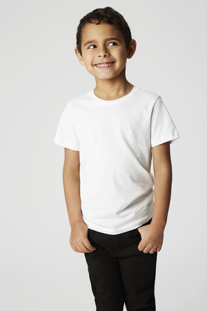 cheeky: Boy with cheeky smile looking away in studio