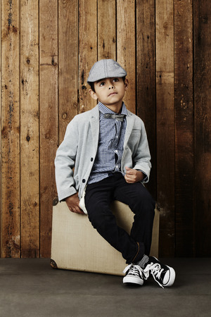 flat cap: Young boy in flat cap sitting on suitcase