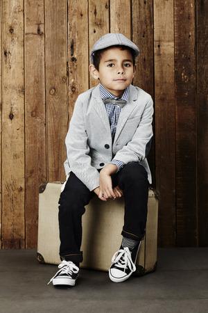 flat cap: Young boy in flat cap sitting on suitcase, portrait