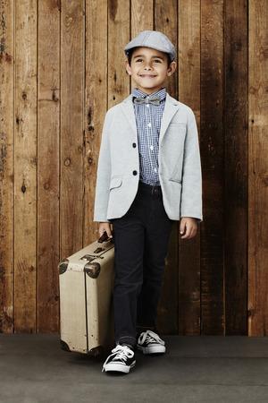 flat cap: Young boy wearing flat cap holding suitcase