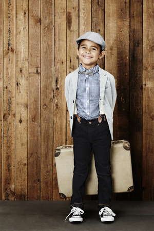 flat cap: Excited boy wearing flat cap and holding suitcase Stock Photo