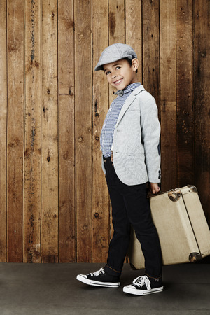 flat cap: Young boy wearing flat cap ready for vacation