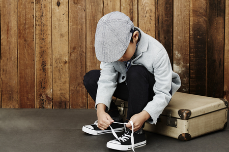 only one boy: Young boy tying shoelace sitting on suitcase