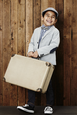 flat cap: Happy young boy wearing flat cap holding suitcase