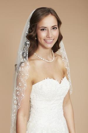 Young bride in wedding dress, studio shot photo