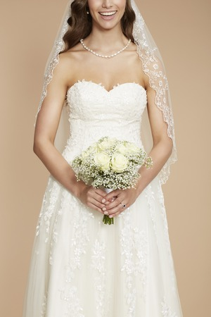 Close up of bride in wedding dress holding bouquet