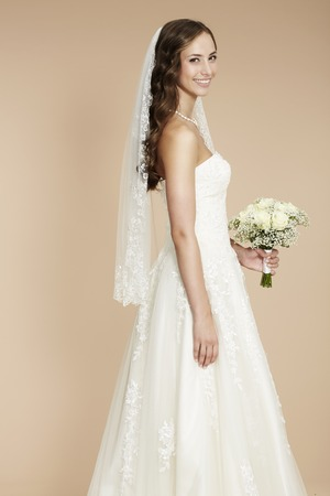 Elegant young bride in wedding dress, studio shot