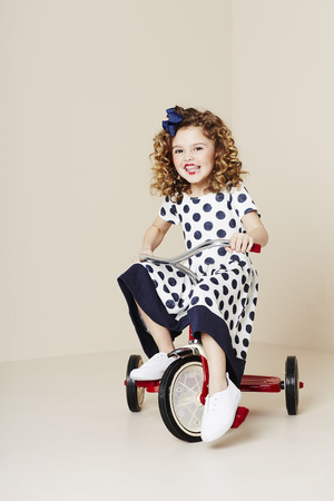 tricycle: Young girl in spotty dress riding tricycle Stock Photo