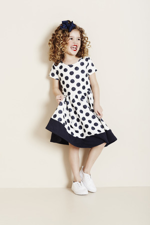 Young girl in spotty dress laughing