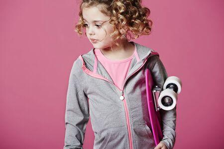 casual hooded top: Chica joven fresco celebraci�n de skateboard, estudio