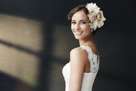 Glamorous ung brud i brudklänning, ler Stockfoto