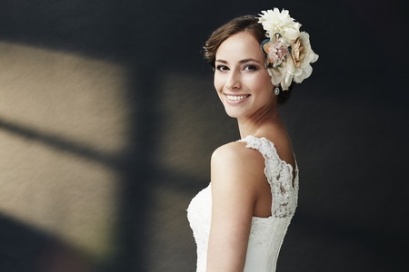 studio portrait: Glamorous young bride in wedding dress, smiling