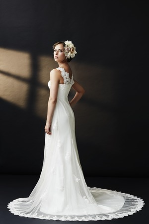 Elegant young bride in wedding dress, studio shot photo