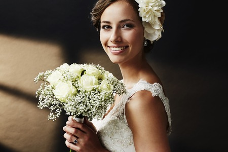 white dresses: Stunning young bride holding bouquet, portrait Stock Photo