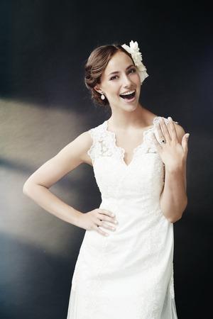 studio portrait: Gorgeous young bride showing wedding ring