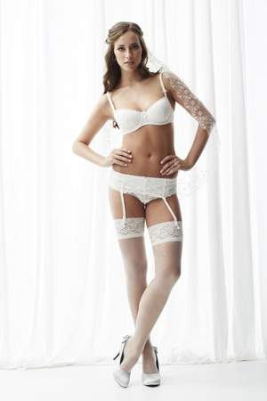 Young bride in white stockings and suspenders, studio photo