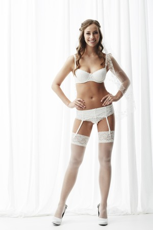 Young bride in white stockings and suspenders, portrait photo