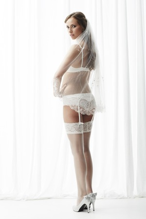 Sexy bride in white stockings and suspenders, portrait