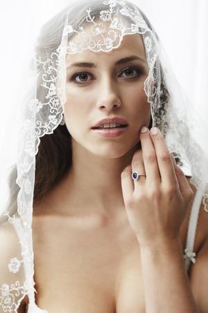 Young bride in wedding veil, studio shot photo