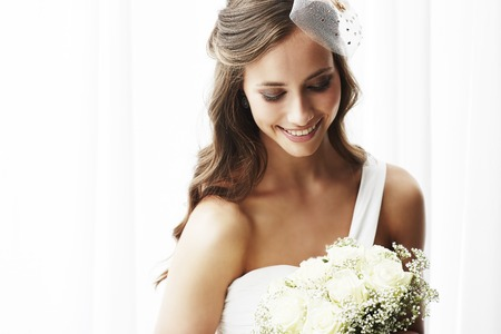 Young bride in wedding dress holding bouquet, studio shot 스톡 콘텐츠
