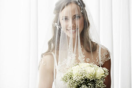 Excited young bride in veil holding bouquet, portrait