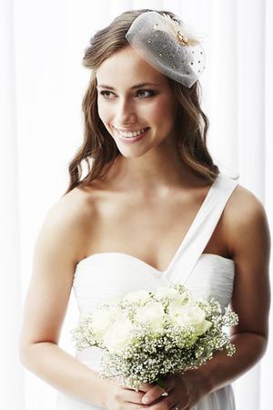 꽃다발, 스튜디오 총을 들고 웨딩 드레스의 젊은 신부 스톡 콘텐츠