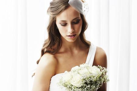 Young bride in wedding dress holding bouquet, studio shot Banque d'images