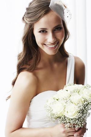wedding bride: Young bride in wedding dress holding bouquet, portrait