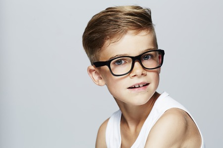 Portrait of young boy wearing glasses, studio