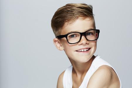 Portrait of young boy wearing glasses, studio