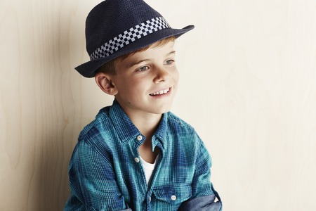 undone: Young boy wearing checked shirt and hat Stock Photo